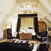 A four poster bed with a black canopy and a black sofa in a converted attic bedroom with trusses