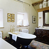 A bathroom in a country house with a freestanding bath tub with feet and brass taps