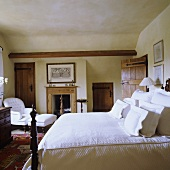 A double bed with white cushions in a country-style bedroom