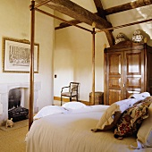 A wooden four-poster bed and an antique wardrobe in a country house-style bedroom under a rustic wooden construction