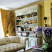 A yellow-painted living room with an antique sofa in front of a light blue bookshelf