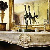 A wooden figure on a mantelpiece in front of a mirror