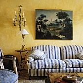 A blue and white striped upholstered sofa with a picture hanging above it and an occasional table with a table lamp in front of a yellow wall