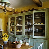 A yellow-painted kitchen with a light blue vintage dresser