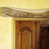 A wooden beam above a door set into a yellow-painted wall