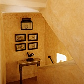 A yellow stairwell with a solid banister and a collection of pictures on a wall above a table on a half landing