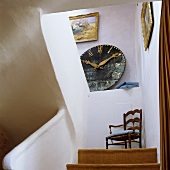 A flight of stairs with a view of a wall clock on a shelf and a wooden chair on the landing in the stairwell of a country house