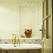 Country house bath with antique brass faucet on a bathtub and earthenware jug in a wall niche