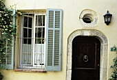Bars in front of a window with grey wooden shutters and a dark wooden front door with a stone facade and a round window above the door in a light yellow facade