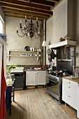 An old kitchen featuring a mixture of styles with grey walls and a chandelier hanging from the rustic wood beam ceiling