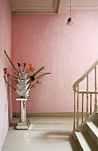 A vase of flowers on a chrome pedestal against a pink wall on a landing