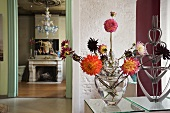 Different coloured dahlias in glass vases and a view into a living room onto the fireplace