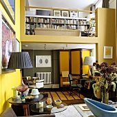 A maisonette apartment - living room with yellow walls and a view onto a gallery with a bookshelf