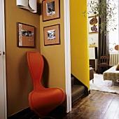 Orangefarbener Designerstuhl in der Ecke vor Treppenaufgang und Blick ins offene Wohnzimmer