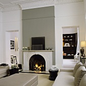A renovated art nouveau-style living room with a grey leather sofa in front of a fireplace in a grey wall and a view of a cupboard