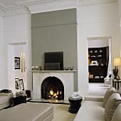 Renovierter Jugendstil Wohnraum mit grauer Ledersofagarnitur vor Kamin in grauer Wand und Blick durch Türöffnung auf Schrank