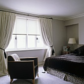A black leather armchair and a double bed with a black fur cover in front of a window with gathered curtains