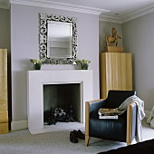 A black leather armchair in front of a fireplace with a silver-framed mirror above it