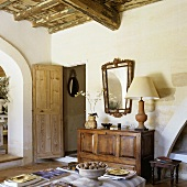 Living room in a Provencal style country home with rustic wooden ceiling and sideboard next to a wide open door