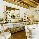 Living room with rustic wooden beams and long half high wall shelf with candelabras in front of a mirror