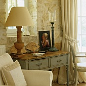 A rustic table lamp with a white shade in a country house-style wall table in front of a plastered natural stone wall