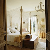 Four poster bed with canopy and hope chest at the foot of the bed in a Mediterranean bedroom