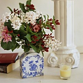 A bunch of flowers in a blue and white porcelain vase and a candle at the foot of a pillar