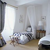 A single bed with a canopy and a stool in a bedroom in a Provençal country house