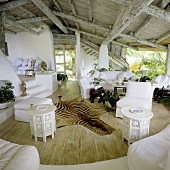 A rustic wood beam ceiling in a tropical one room house with an open view and an animal skin on the floor