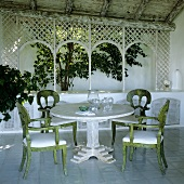Green curved wooden chairs around a round table and wooden lattice wall with rounded arches on a veranda