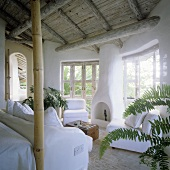A living room with a rustic wooden ceiling in a tropical holiday home with a fireplace and a white sofa