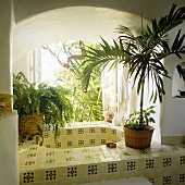A tiled sink in a arched wall niche with a window and view of the garden