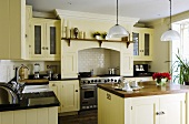 A light yellow kitchen in an English country house with an island counter