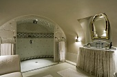 An elegant bathroom with a vaulted ceiling, a luxury shower area and a mirror above a marble topped washstand