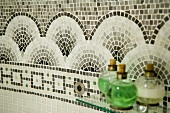 Glass bottles on a glass shelf in front of a circular design made of mosaic tiles on a wall
