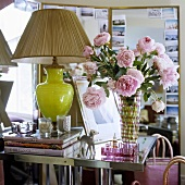 A table lamp with a green glass base and a pleated shade next to a bunch of roses in a glass vase on a side table