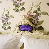 Sleeping mask on a headboard in front of wallpaper with a floral pattern on the wall
