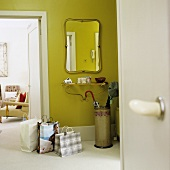 Shopping bags in front of an open door and a hall mirror with a brass shelf below it on a green-painted wall