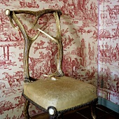 Upholstered chair made of antlers in front of patterned wallpaper on a wall