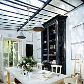 A dining room and a high black crockery cupboard in a glass extension with a door into the garden
