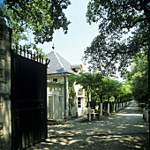 Opened metal gate with a view of a country home and alley