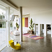 A Mediterranean house - a yellow plastic chair in front of a concrete pillar and a view through a row of arches into an open-plan living room