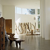 A Mediterranean designer house - a rustic antique chair on polished floor screed in a open-plan living room