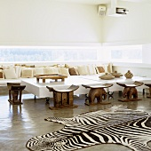 A Mediterranean designer house - a zebra rug in front of ethnic wooden stools and a designer coffee table