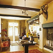 A yellow living room with a wood beam ceiling and a stuffed animal head on the wall above the fireplace