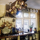 Copper pots hanging from a wooden ceiling beam in the kitchen of a country house