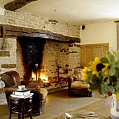 A cosy corner in a country house - a leather armchair in front of a natural stone fireplace with a fire burning in the grate