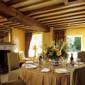 A table laid in a room with a wood beam ceiling in a yellow-painted living room in a country house