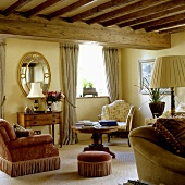 A comfortable corner of a living room with a wood beam ceiling, antique upholstered armchairs and a foot stool next to a wooden table