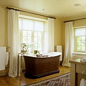 A bathroom in an old English country house with a free-standing bathtub and antique standing taps